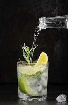 暗いテーブルの上のライムレモネードのグラス、夏の飲み物。ガラスに純粋なミネラルウォーターを注ぎます。垂直フレーム、セレクティブフォーカス。ライム、タラゴン、角氷を使った自家製ドリンク。冷たい新鮮な飲み物のアイデア