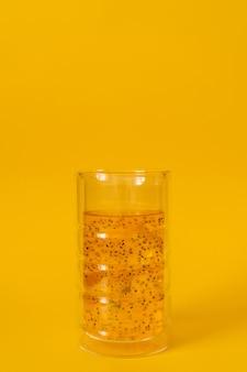 黄色の背景にバジルの種とマンゴードリンクのガラス。