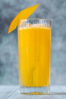 新鮮なマンゴーのスライスを添えたマンゴーラムクーラーカクテルのグラス