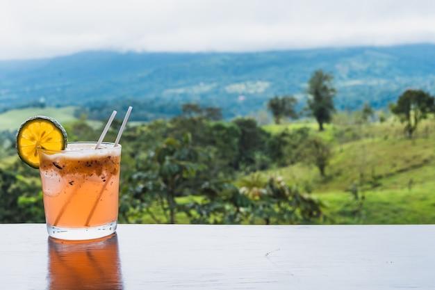 Стакан мишелады со льдом и лимоном на столе в джунглях. коста-рика гастрономия