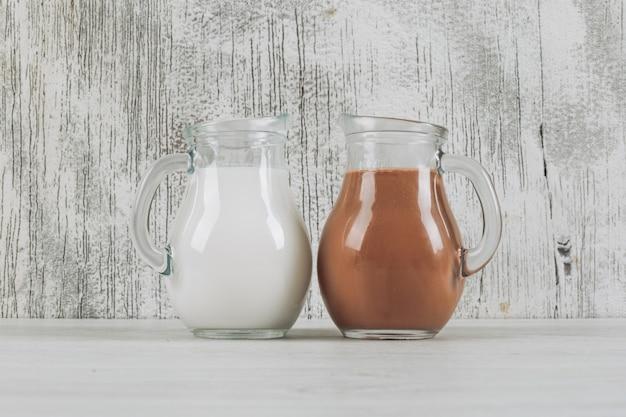 흰색 나무 배경에 우유와 코코아 우유 측면보기의 유리