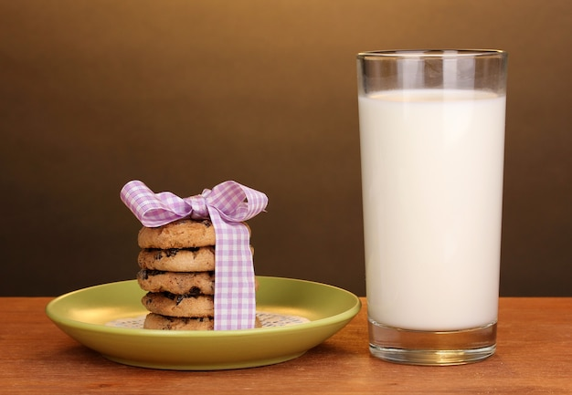 Стакан молока и печенья на деревянном столе на коричневом фоне