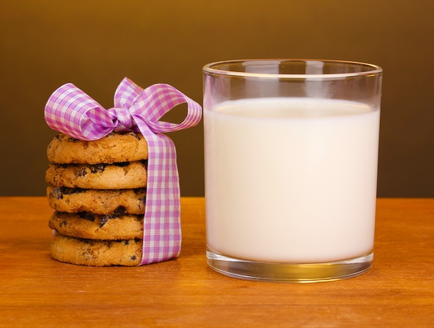 茶色の表面の木製のテーブルにミルクとクッキーのガラス