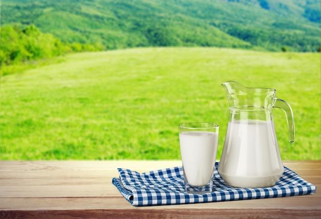 천과 배경이 있는 테이블에 우유와 항아리 유리