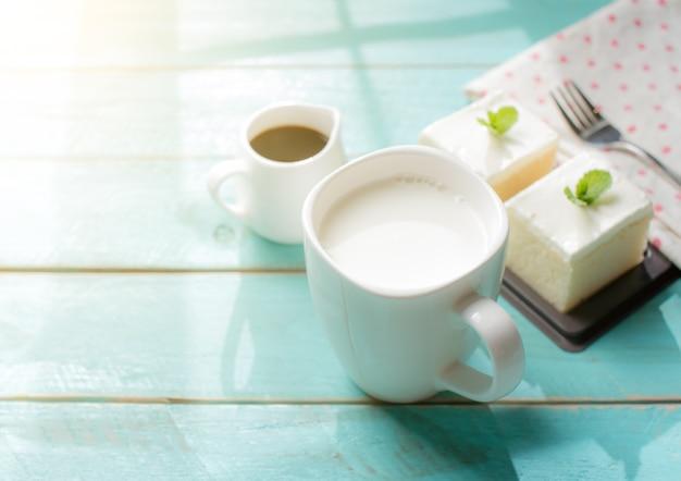 窓枠からの影を持つ木製テーブル上で美味しいミルクとミルクケーキのガラス