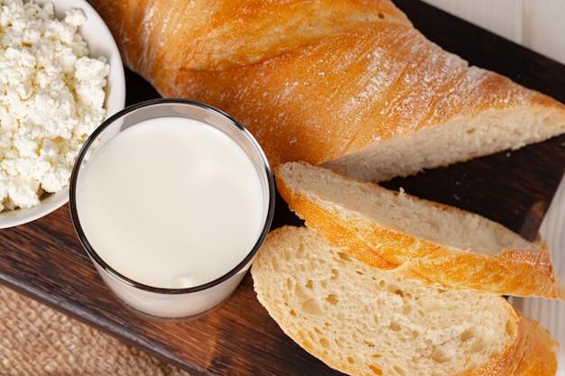 牛乳のガラス、カッテージチーズのボウル、テーブルの上のパン