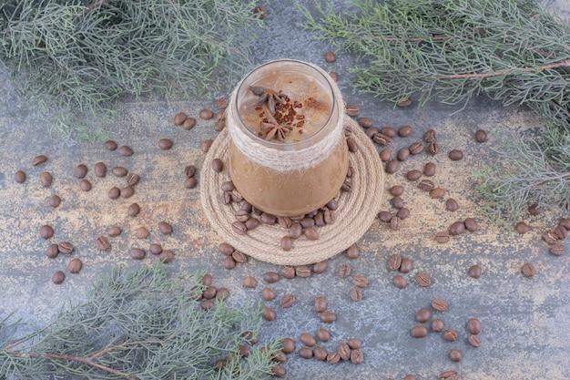Стакан молочного кофе с кофейными зернами на мраморной поверхности. фото высокого качества