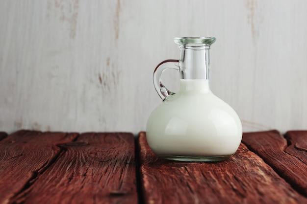오래 된 나무 테이블에 서있는 우유의 유리