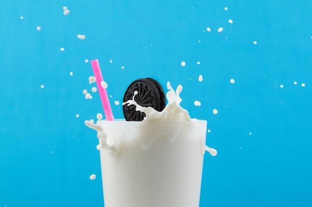 ピンクのストローとクッキーが飛び散るミルクのグラス