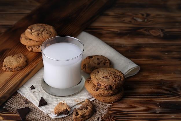 어두운 빈티지 나무 테이블에 식욕을 돋우는 맛있는 달콤한 수제 초콜릿 칩과 함께 우유 한 잔