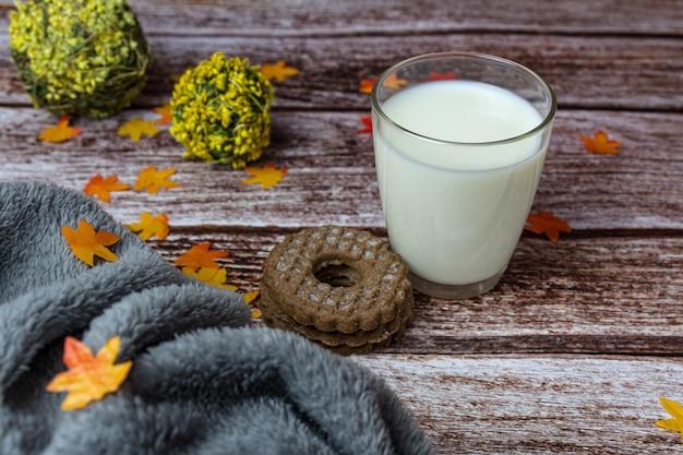 Стакан молока с печеньем на доске в осеннем стиле