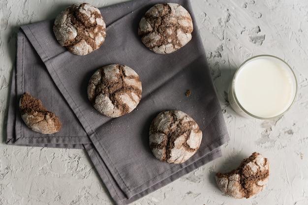 灰色の背景にひびの入ったチョコレートクッキーとミルクのガラス。素朴なスタイル