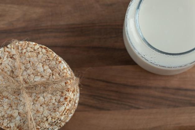 木の板にクリスプブレッドと牛乳のガラス