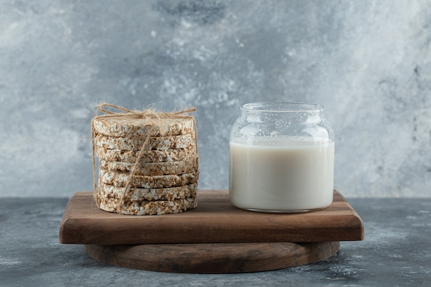 木の板においしいクリスプブレッドと牛乳のガラス