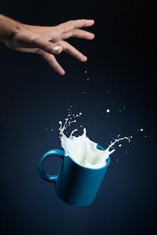 진한 파란색 배경에 손에서 떨어지는 스플래시와 우유의 유리.