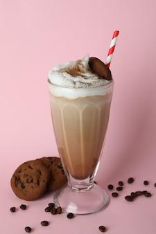 Стакан молочного коктейля, кофейных зерен и печенья на розовом фоне