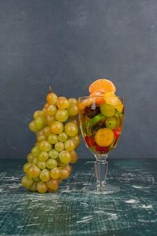 大理石のテーブルの上の混合果物とブドウのクラスターのガラス。