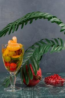 Стакан смешанных фруктов и граната с семенами на мраморном столе.
