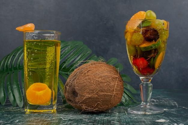 大理石のテーブルにミックスフルーツ、ジュース、ココナッツのグラス。