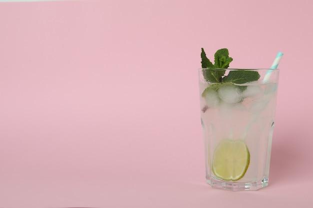 ピンクの表面にモヒートカクテルのグラス