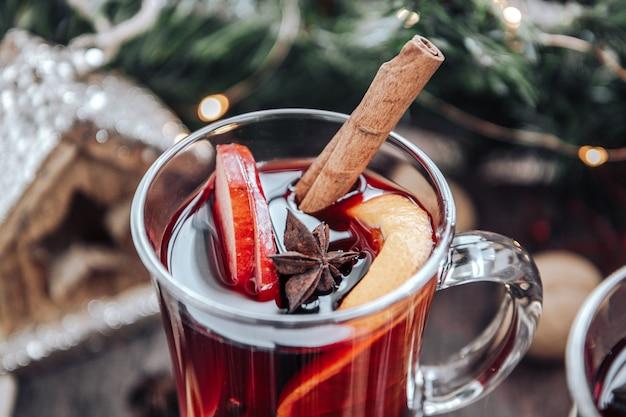 오렌지, 사과, 향신료와 mulled 와인의 유리. 온난화 크리스마스 음료를 닫습니다.