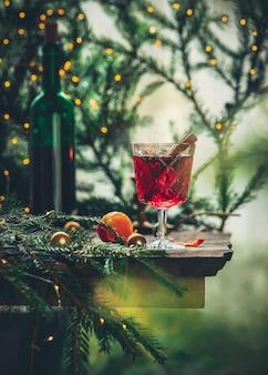 松の枝とフェアリーライトとホットワインのグラス