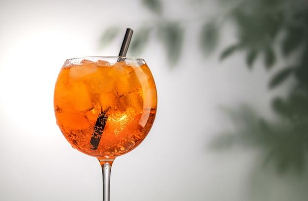 Стакан апельсинового коктейля aperol spritz на фоне расфокусированных листьев
