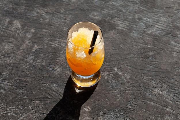 暗い背景にオレンジグラニザードのガラスオレンジジュースまたはシロップ飲料と砕いた氷