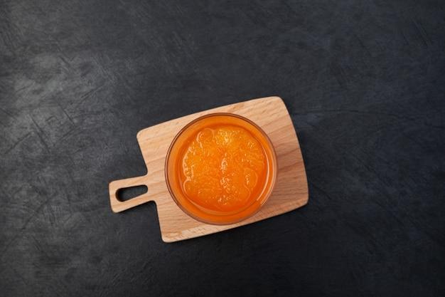 暗い背景にオレンジグラニザードのガラスオレンジジュースと砕いた氷