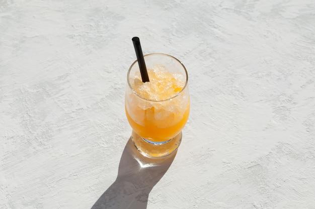 ライトテーブル上のオレンジグラニザードのガラスオレンジジュースまたはシロップ飲料と砕いた氷