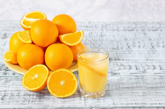 オレンジジュースのガラスと木製のテーブルにオレンジのプレート