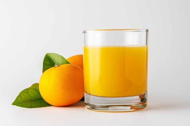 Стакан апельсинового сока и апельсиновых фруктов на белом фоне.