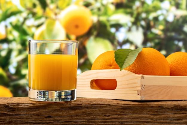 Стакан апельсинового сока и апельсиновых фруктов на природе.