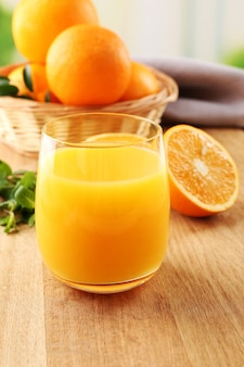 オレンジジュースのガラスと木製のテーブルにオレンジと籐のバスケット