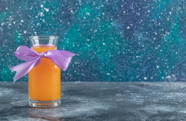 大理石のテーブルにオレンジジュースのガラス。