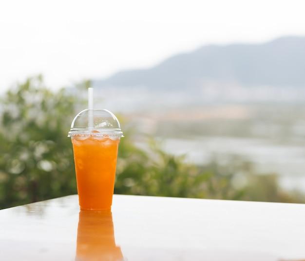 屋外カフェのテーブルにオレンジジュースのガラス