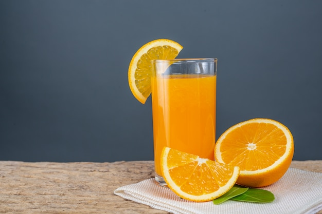 Стекло апельсинового сока помещенное на древесине.