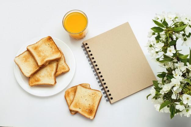 Стакан апельсинового сока, тосты на белой тарелке, блокнот и ветка с цветами на белом фоне. концепция здорового весеннего завтрака