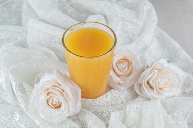 白い布の上に花とオレンジジュースのガラス