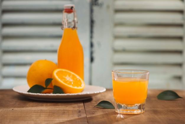 木製の背景に新鮮な果物とオレンジ ジュースのグラス