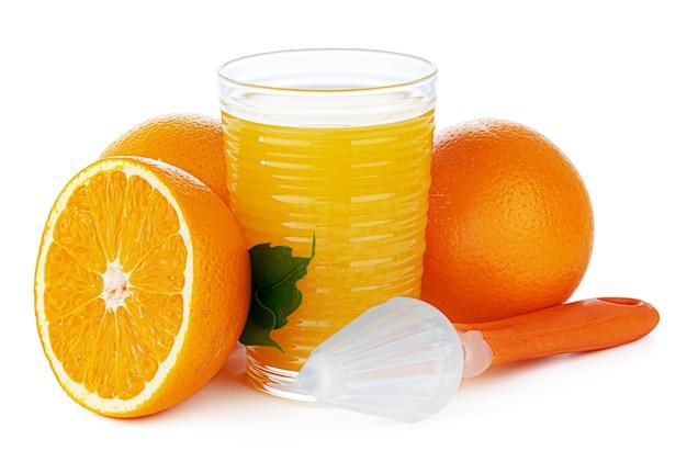 白で隔離される絞り器とオレンジジュースのガラス