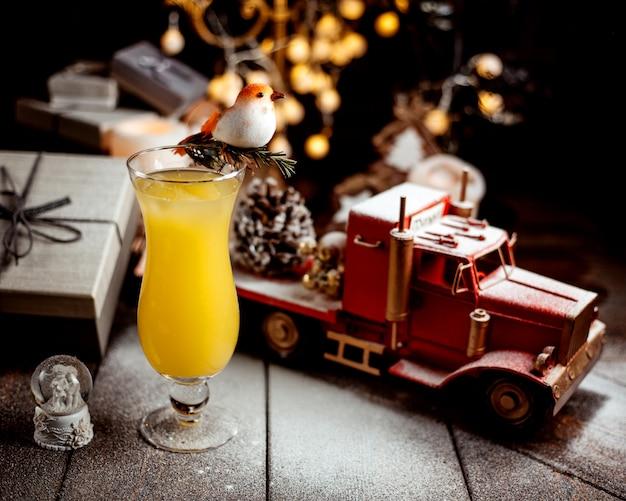 おもちゃのトラックでオレンジジュースのガラス