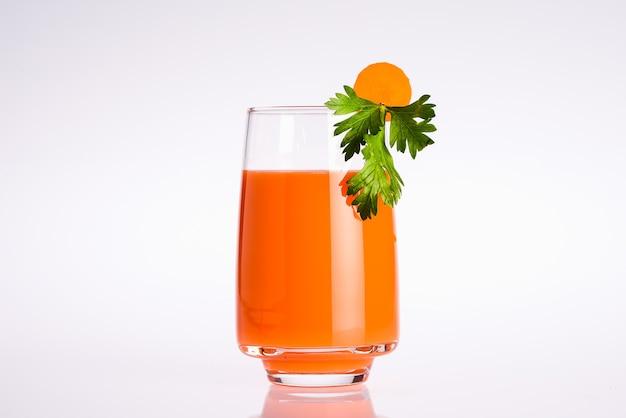白い背景にニンジンとパセリの葉のスライスとオレンジ色の有機野菜ジュースのガラス
