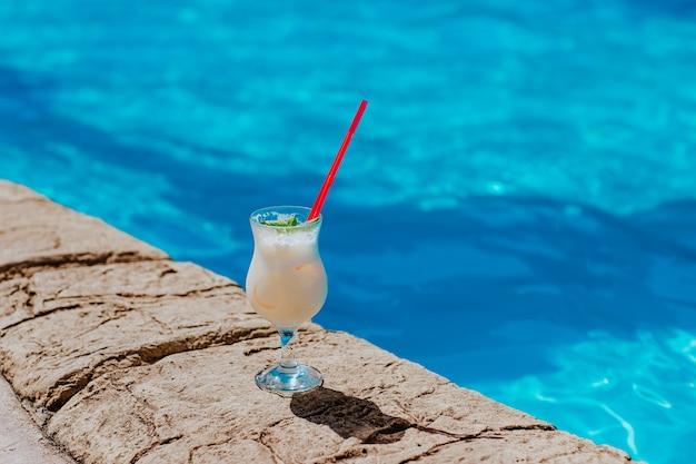 Стакан коктейля пина колада, стоящий у бассейна