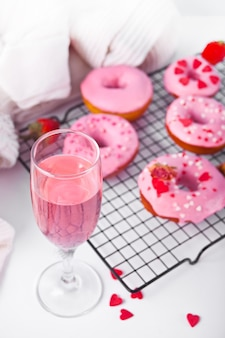 베이킹 선반에 핑크 와인 또는 샴페인과 핑크 도넛의 유리. 발렌타인 데이 개념.