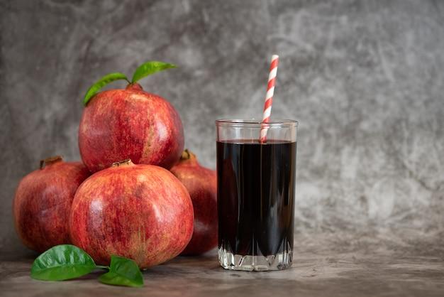 ザクロジュースと灰色の背景にザクロの果実のガラス。コピースペース付き
