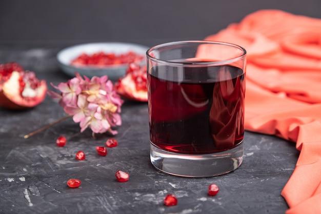 빨간색 섬유와 검은 콘크리트 배경에 석류 주스의 유리.