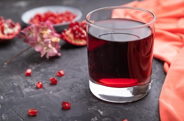 빨간색 섬유와 검은 콘크리트 표면에 석류 주스의 유리