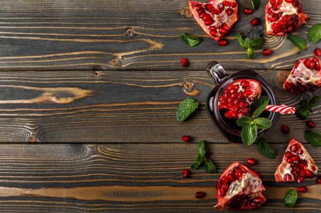 Стекло гранатового сока с свежими плодоовощами граната и мяты на деревянном столе.