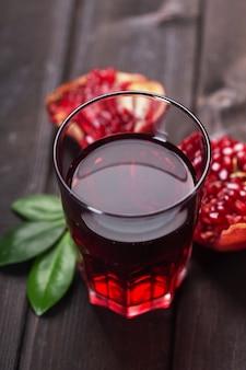 어두운 나무 테이블에 석류 과일의 잎으로 조각으로 석류 주스 한 잔